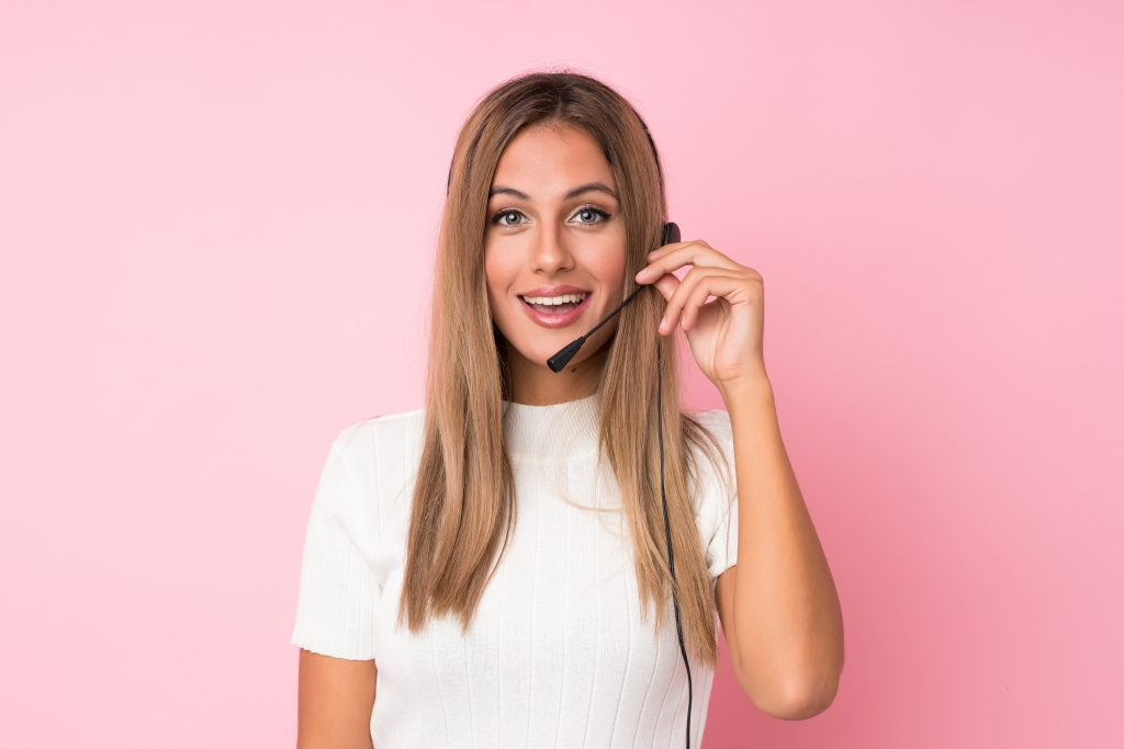 Young blonde woman over isolated pink background working with headset in call centre